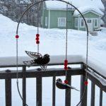 Au balcon d'une petite maison en bois coloré finlandaise est suspendu un mobile en métal représentant deux oiseaux. Il tourne lentement au rythme des bourrasques de vent.