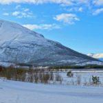 La Laponie côté Norvège est montagneuse. En arrière-plan des plaines se dressent les sommets enneigés qui contrastent avec le bleu du ciel.