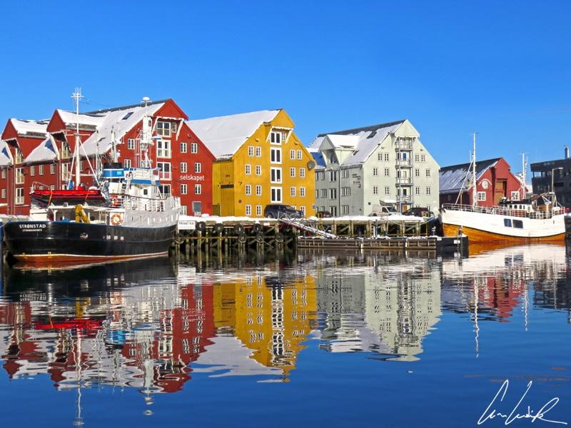 Sur le port, dans la douce lumière de fin d'après-midi, les façades colorées (rouge, jaune et verte) des maisons en bois de Tromsø se reflètent dans l'eau.