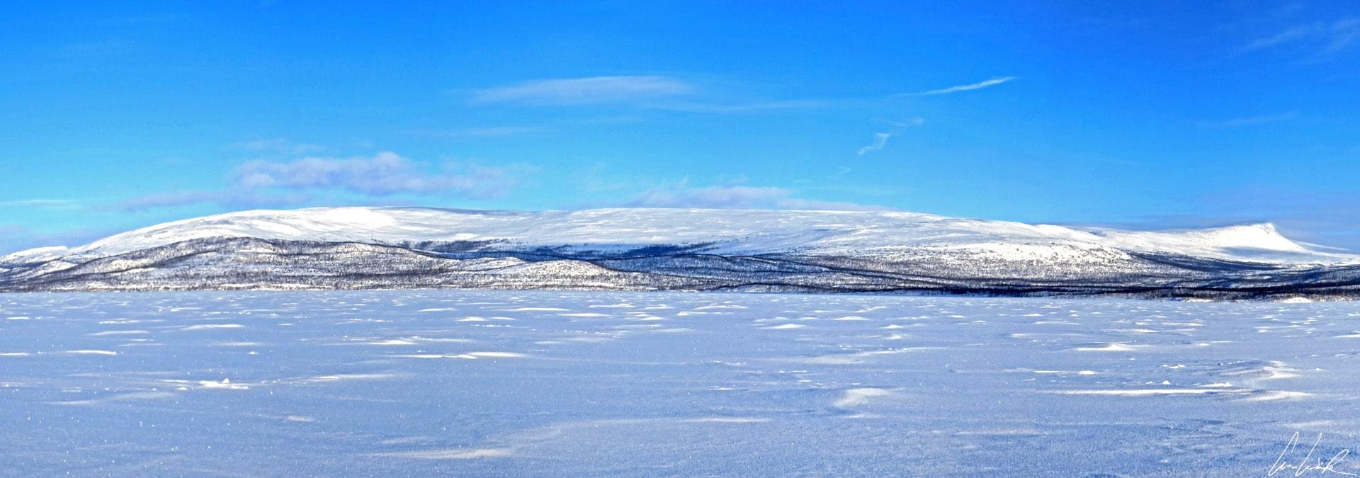 La magnifique vue panoramique d'un immense lac gelé en Laponie. Le cadre naturel est désertique et d'une blancheur immaculée aussi loin que porte votre regard.