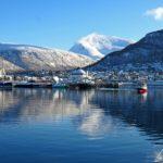 En fin d'après-midi, un bateau de pêche rouge rentre au port de Tromsø tandis que d'autres bateaux sont déjà à quai.