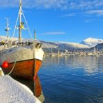 Un imposant bateau avec sa coque en bois est à quai dans le port de Tromsø. Il se reflète dans l'eau.