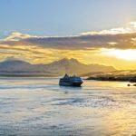Le célèbre Hurtigruten, l'Express Côtier de Norvège, rentre au port de Tromsø au soleil couchant avec en toile de fond les montagnes enneigées.