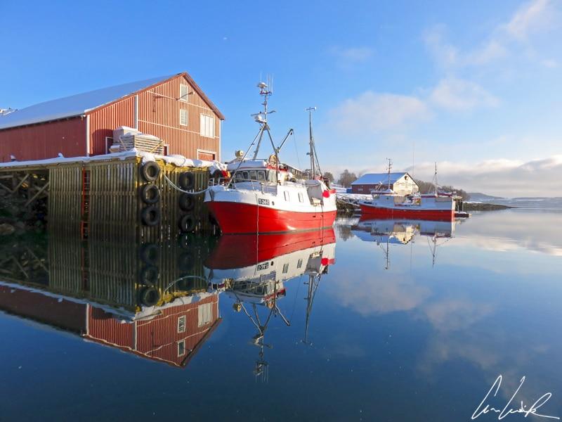 Dans la baie d'Eidkjosen en Norvège sont amarrés de nombreux bateaux de pêche proches des hangars en bois colorés. L'effet miroir sur l'eau est saisissant.