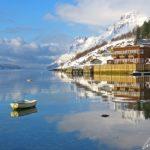 Une barque esseulée dans l'Ersfjord en Norvège se reflète dans l'eau ainsi que les hangars en bois colorés en bordure de fjord.