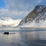 Seuls sur la plage recouverte de glace au bord de l'océan arctique en Norvège. Les sommets qui bordent la plage sont recouverts de neige.