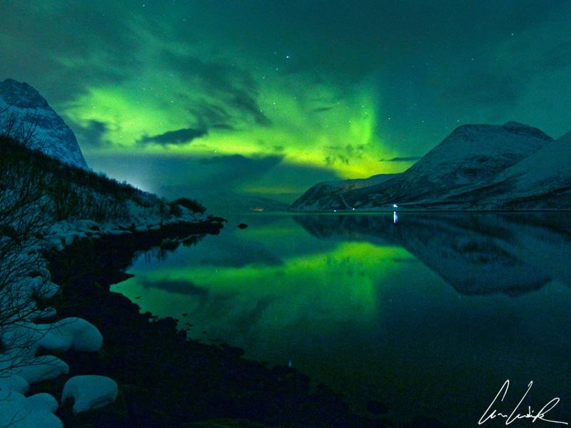Dans le magnifique Ersfjord en Norvège, les aurores boréales se forment pile dans l'alignement du fjord et se reflètent dans l'eau.