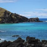 Sur l'île de Pâques, la côte est rocheuse et balayée par les vagues et le vent. Le bleu de l'océan contraste avec le noir des falaises volcaniques