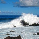 Sur l'île de Pâques, les vagues battent les flancs d'une côte déchiquetée. Le noir des roches volcaniques contraste avec le bleu de l'océan