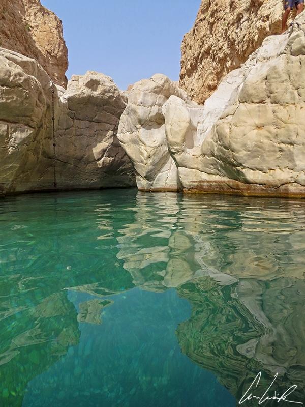 Les gros rochers blancs et les falaises ocres se reflètent dans les piscines. L'eau est si claire qu'on peut voir le fond de galets.
