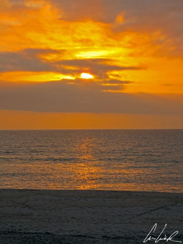 A Cape Cross, sur la plage face à l'océan Atlantique, le ciel et les nombreux nuages se teintent d'orangé au fur et à mesure que le soleil décline.