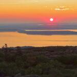 Le lever de soleil sur le parc national d'Acadia baigne le ciel de teintes orangées. On commence à distinguer l'océan et les Porcupine Islands