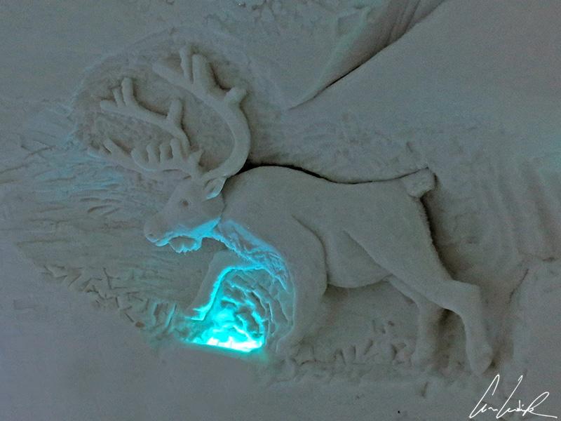 Des sculptures éphémères ont été créées in situ à l'entrée de l'hôtel de glace d'Enontekiö. Ici un renne baignant dans un éclairage bleuté.