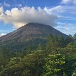 La silhouette conique du volcan Arenal est souvent revêtue d'un voile de brume au sommet. On a l'impression qu'un chapeau nuageux est délicatement posé sur le cône.