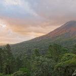 Au coucher du soleil des couleurs de feu s'étendent sur le flanc du volcan Arenal et sur la cime des arbres de la forêt.