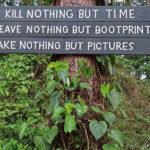 Panneau informatif sur les sentiers de randonnée près du volcan Arenal: ne tuez rien à part le temps ; ne laissez rien à part vos empreintes de pas; ne prenez rien à part des photos .