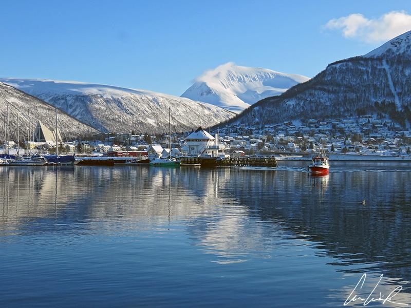 Depuis le port de Tromsø, la cathédrale Arctique et les montagnes environnantes qui se reflètent dans les eaux sombres du port.