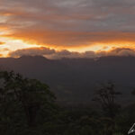 At Tenorio volcano park, the sky and clouds are painted with beautiful orange and reddish colors at sunset.